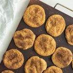 Baked Cinnamon Sugar Cookies on a baking stone with a white towel behind on a white surface (vertical with title overlay)
