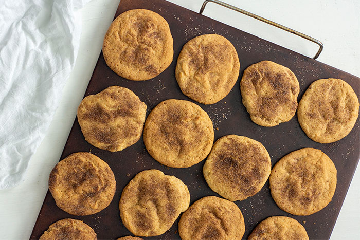 Baked Cinnamon Sugar Cookies on a baking stone with a white towel behind on a white surface