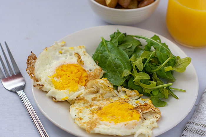 Fried Eggs Over-Hard on a white plate next to greens with breakfast potatoes and orange juice in the background (horizontal)