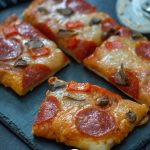 Pieces of pizza topped with sauce, cheese, pepperoni, and mushrooms on a slate serving plate next to a pizza cutter on a wooden surface (vertical with title overlay)