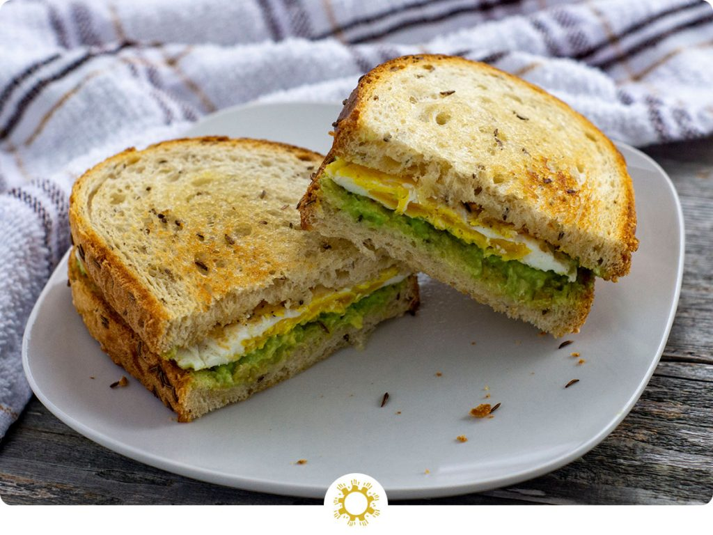 Avocado egg toast of toasted bread with fried egg and smashed avocado as a sandwich sliced in half of a white plate with a white and brown towel behind all on a wooden surface (with logo overlay)