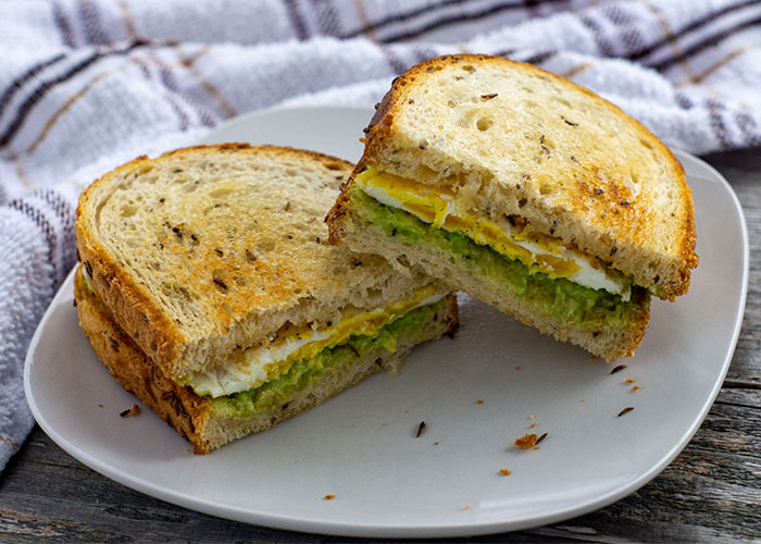 Avocado egg toast of toasted bread with fried egg and smashed avocado as a sandwich sliced in half of a white plate with a white and brown towel behind all on a wooden surface