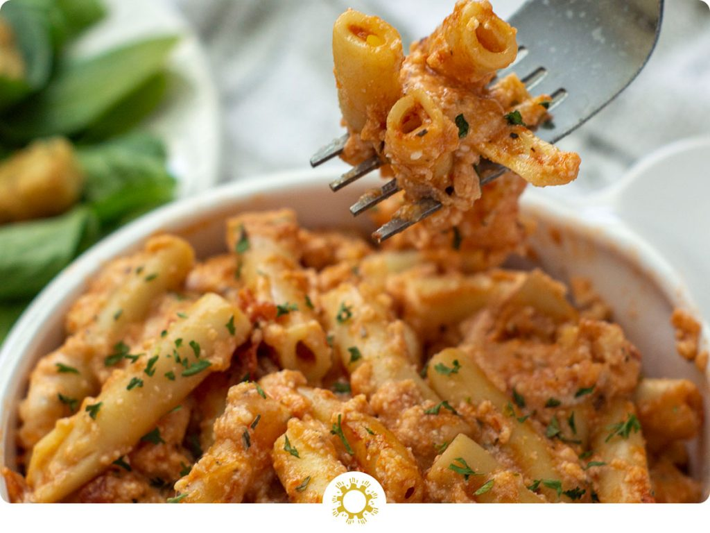Baked ziti in a white bowl (with logo overlay)