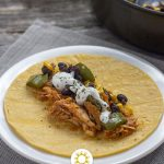 BBQ chicken and black bean taco fillings on a corn tortilla on a round white plate on a grey placemat next to a nonstick skillet with taco fillings all on a wooden surface (vertical with title overlay)