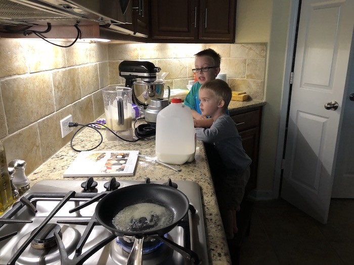 Two young boys pouring ingredients into the blender at a countertop