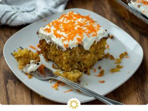 A slice of Carrot Cake with Pineapple Filling and cream cheese frosting on a white plate with a metal fork next to a white towel and the pan of cake in the background on a wooden surface (with logo overlay)