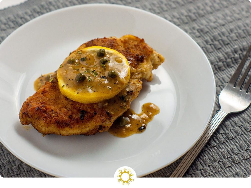 Chicken piccata topped with lemon on a round white plate with a fork and grey placemat (with logo overlay)