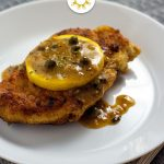 Chicken piccata topped with lemon on a round white plate with a fork and grey placemat (vertical with title overlay)