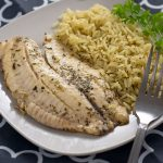Cilantro and lime juice covered fish fillets next to cilantro lime rice with a sprig of fresh cilantro on a square white plate with a stainless steel fork on a white and grey placemat on a wooden surface (vertical with title overlay)
