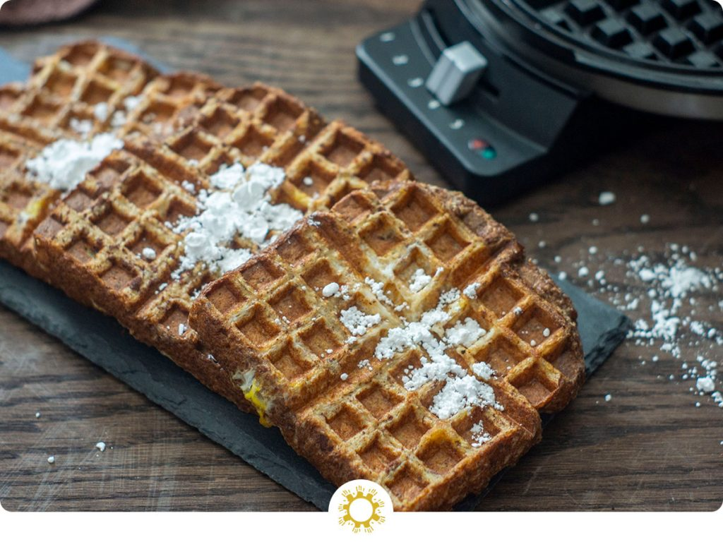 Pieces of French Toast Waffles sprinkled with powdered sugar at a diagonal on a slate tray with a waffle iron behind all on a wooden surface (with logo overlay)