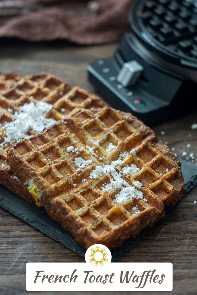 Pieces of French Toast Waffles sprinkled with powdered sugar at a diagonal on a slate tray with a waffle iron behind all on a wooden surface (vertical with title overlay)