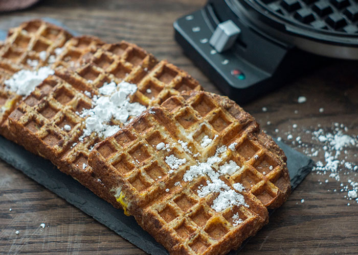 Pieces of French Toast Waffles sprinkled with powdered sugar at a diagonal on a slate tray with a waffle iron behind all on a wooden surface