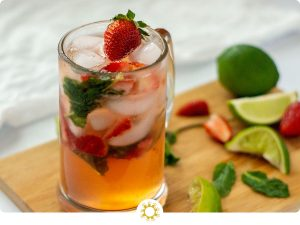 Strawberry mojito in a class on a bamboo cutting board with logo overlay