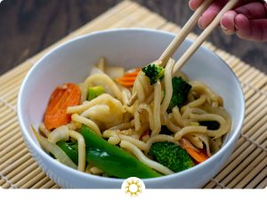 Round white bowl of vegetable lo mein with a pair of chopsticks pulling out some noodles, onion, and broccoli on top of a bamboo placement on a wooden surface (with logo overlay)