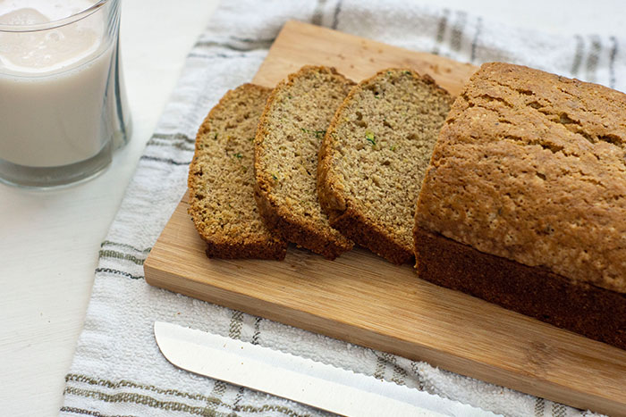 Sliced zucchini bread on a wooden cutting board next to a bread knife and glass of milk