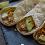 Avocado fish tacos rolled up and ready to eat with title overlay