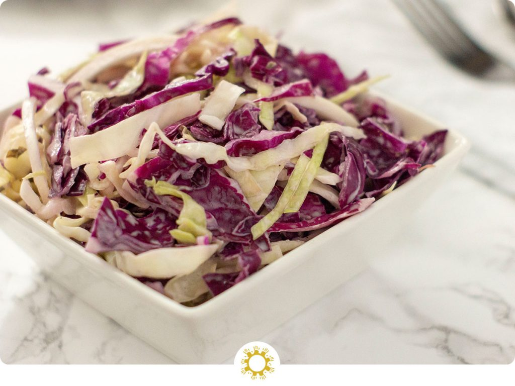 Coleslaw in a square white bowl on a white and grey marbled background (with logo overlay)