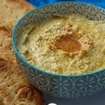 Garlic hummus in a blue patterned bowl with pita bread on the side (with title overlay)