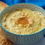 Garlic hummus in a blue patterned bowl with pita bread on the side
