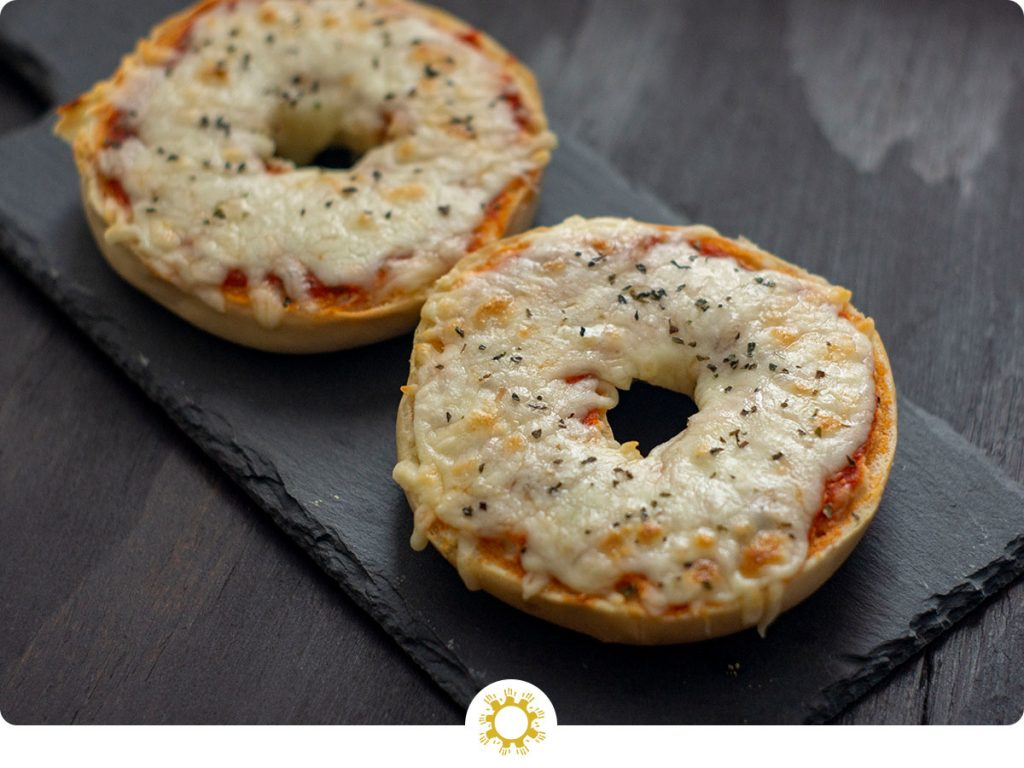 Homemade Pizza Bagels covered with layers of sauce and cheese on a slate serving tray on a dark wooden surface (with logo overlay)