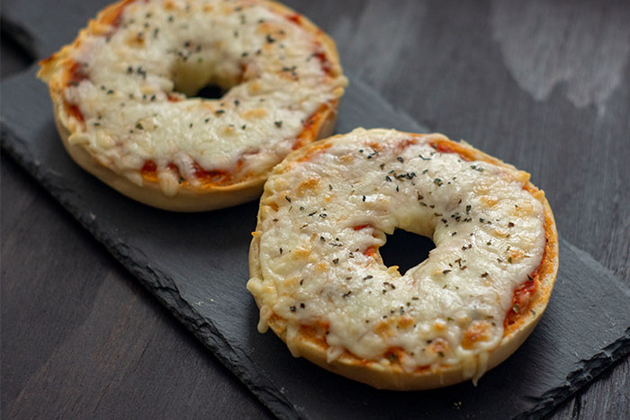Homemade Pizza Bagels covered with layers of sauce and cheese on a slate serving tray on a dark wooden surface