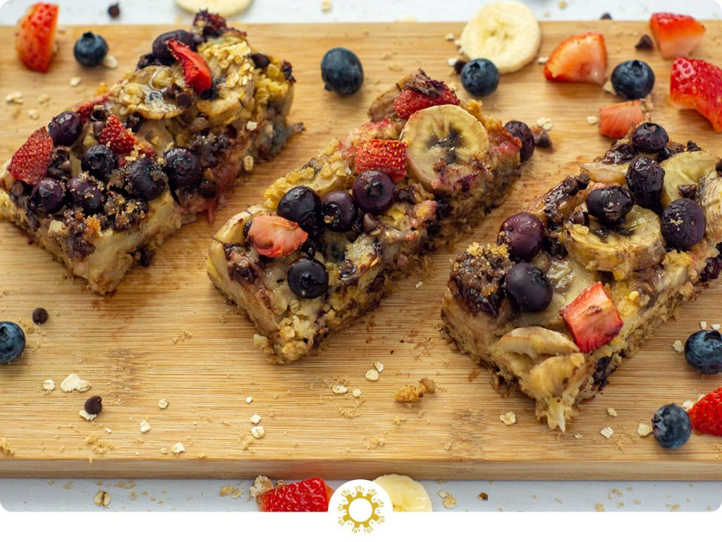 3 sliced oatmeal bars on a bamboo cutting board with extra fruit around the edge (with logo overlay)