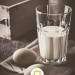 Two eggs and a glass of milk on a grey napkin on a wooden surface (vertical with title overlay)