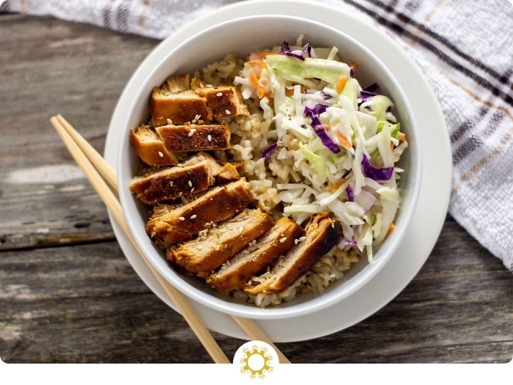 Sweet and sour chicken in rice with a scoop of coleslaw in a white round bowl on top of a white round plate with bamboo chopsticks on the plate and a white and brown towel behind all on a wooden surface (with logo overlay)