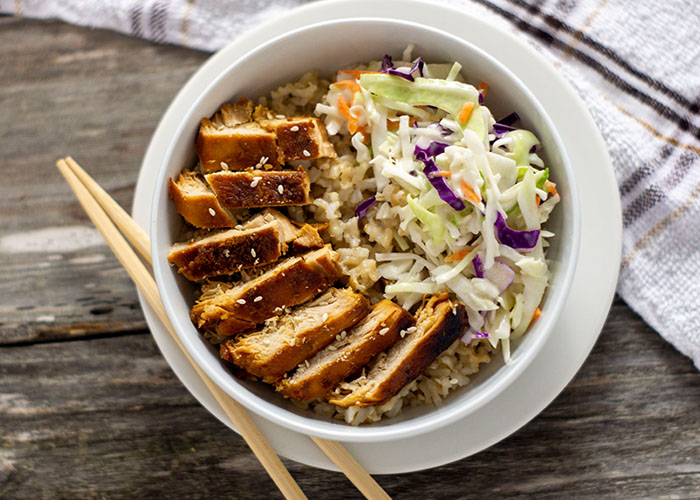 Sweet and sour chicken in rice with a scoop of coleslaw in a white round bowl on top of a white round plate with bamboo chopsticks on the plate and a white and brown towel behind all on a wooden surface