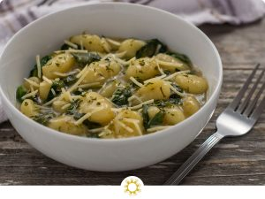Toasted gnocchi with spinach garnished with parmesan cheese and parsley in a round white bowl with a stainless steel fork in front and a white and brown towel behind all on a wooden surface (with logo overlay)