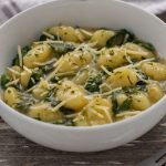 Toasted gnocchi with spinach garnished with parmesan cheese and parsley in a round white bowl with a stainless steel fork in front and a white and brown towel behind all on a wooden surface (vertical with title overlay)