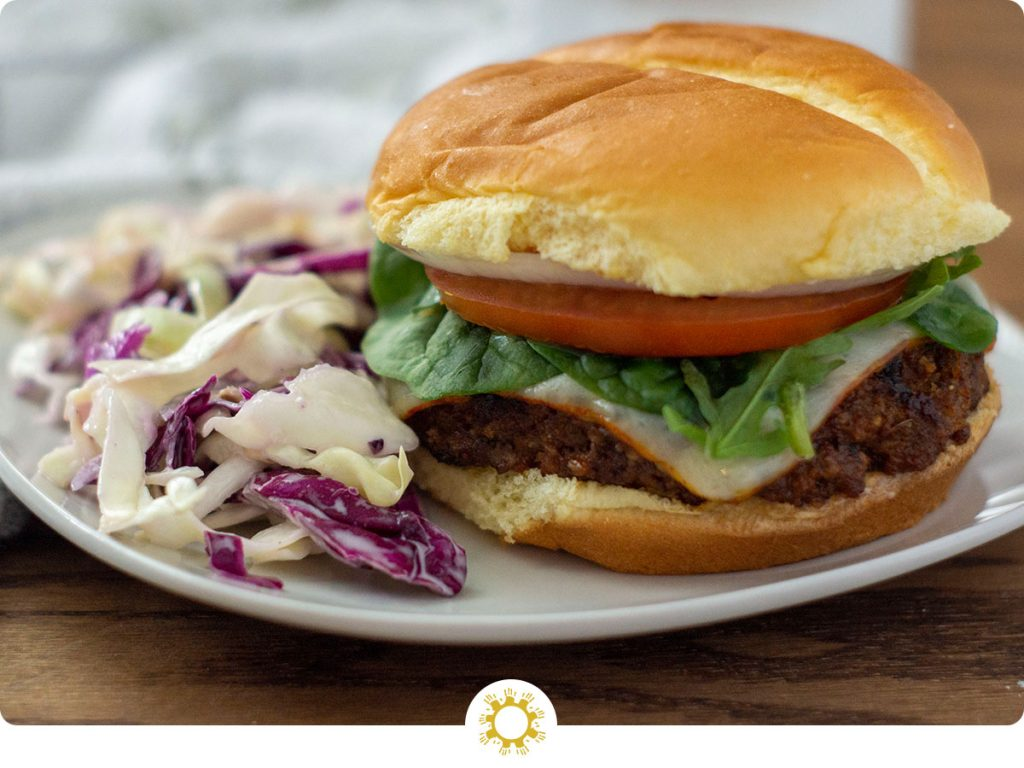 BBQ burger on a white plate next to coleslaw on a wooden background (with logo overlay)