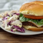 BBQ burger on a white plate next to coleslaw on a wooden background