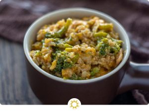 Cheesy Rice Casserole with Chicken and Broccoli in a brown serving dish with a brown and white towel behind all on a wooden surface (with logo overlay)