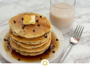Stack of five chocolate chip pancakes topped with a pat of butter and syrup on a round white plate next to a stainless steel fork and a glass of milk all on a white and grey marble surface (with logo overlay)