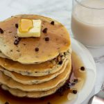 Stack of five chocolate chip pancakes topped with a pat of butter and syrup on a round white plate next to a stainless steel fork and a glass of milk all on a white and grey marble surface (vertical with title overlay)