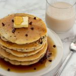 Stack of five chocolate chip pancakes topped with a pat of butter and syrup on a round white plate next to a stainless steel fork and a glass of milk all on a white and grey marble surface