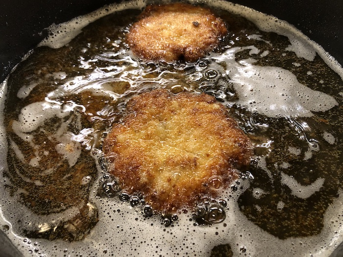 Fish patties in oil in a large skillet