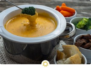 White and stainless steel fondue pot on top of a white knit potholder filled with garlic and herb cheese fondue with a piece of broccoli being dipped in the cheese next to white bowls with carrots, broccoli, beef tips, and bread all on a wooden surface (with logo overlay)