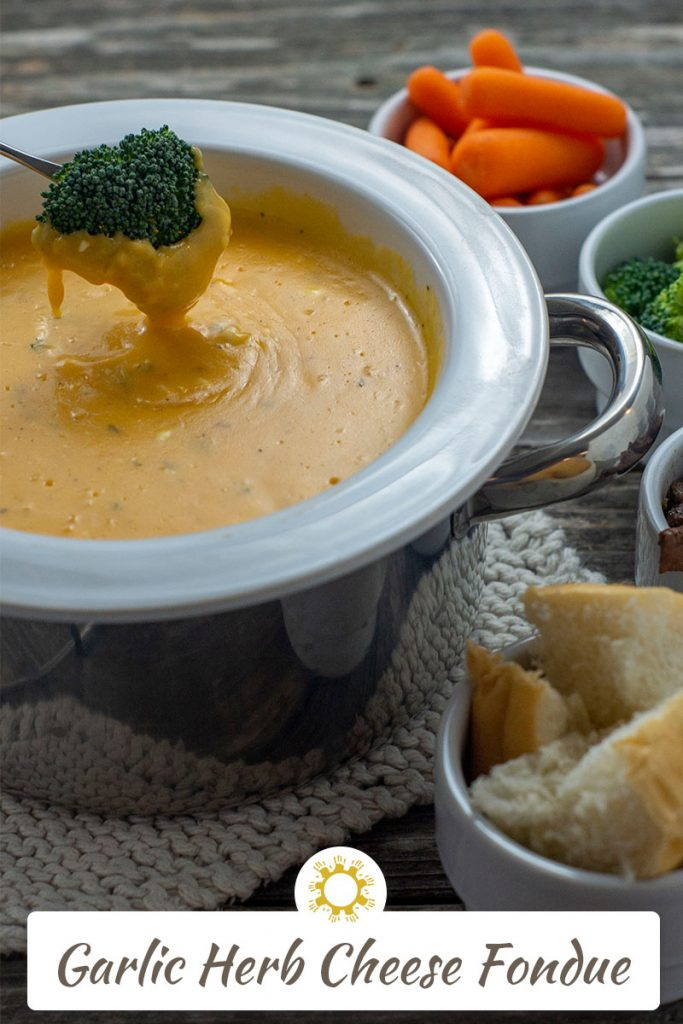 White and stainless steel fondue pot on top of a white knit potholder filled with garlic and herb cheese fondue with a piece of broccoli being dipped in the cheese next to white bowls with carrots, broccoli, beef tips, and bread all on a wooden surface (vertical with title overlay)