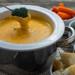 White and stainless steel fondue pot on top of a white knit potholder filled with garlic and herb cheese fondue with a piece of broccoli being dipped in the cheese next to white bowls with carrots, broccoli, beef tips, and bread all on a wooden surface