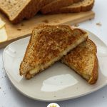 Classic Grilled Cheese Sandwich wedges on a round white plate with sliced bread and cheese behind all on a white surface (vertical with title overlay)