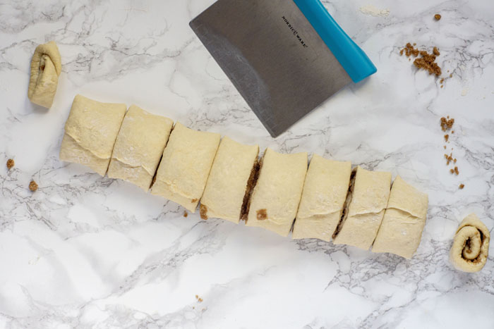 Log of rolled dough filled with cinnamon sugar mixture cut into 8 pieces next to a pastry butter on a white and grey marble surface