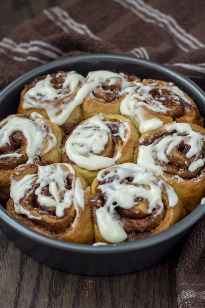No Yeast Jumbo Cinnamon Rolls covered with cream cheese frosting in a round metal pan with a brown and white towel behind on a wooden surface (vertical)