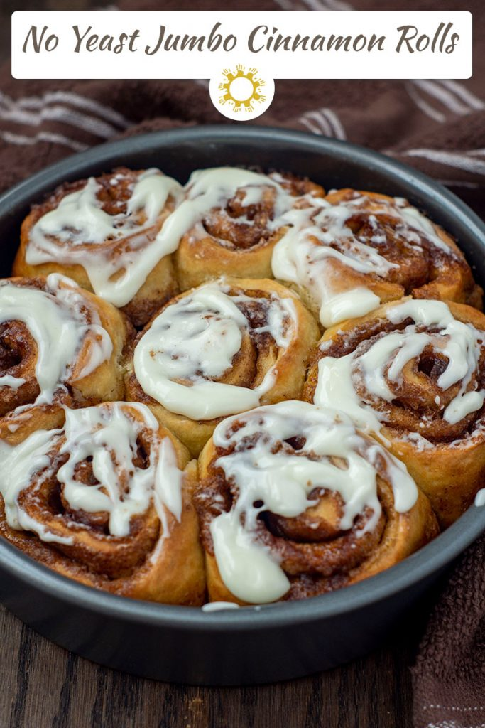 No Yeast Jumbo Cinnamon Rolls covered with cream cheese frosting in a round metal pan with a brown and white towel behind on a wooden surface (vertical with title overlay)