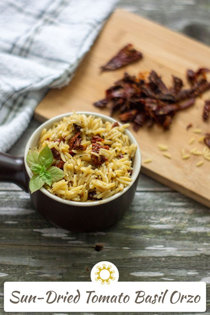 Sun-Dried Tomatoes with Basil in Orzo Pasta in a small brown dish with extra ingredients in the background (with title overlay)