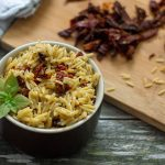 Sun-Dried Tomatoes with Basil in Orzo Pasta in a small brown dish with extra ingredients in the background