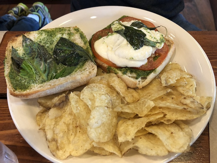 My Vacation in Food: Part 3: Caprese sandwich with potato chips on a round white plate
