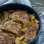 Cooked seasoned pork chops on a bed of cooked sliced onions and apples with an herb juice in a large skillet on top of a white and grey towel all on a wooden surface (vertical with title overlay)