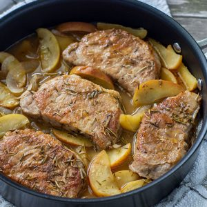 Cooked seasoned pork chops on a bed of cooked sliced onions and apples with an herb juice in a large skillet on top of a white and grey towel all on a wooden surface